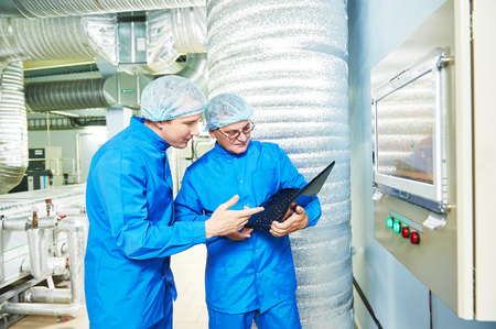 Two pharmaceutical technician male workers in air conditioning production line hall at pharmacy industry manufacture factory using notebook computer Foto de archivo