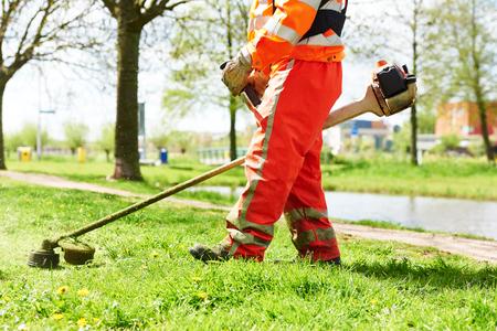 mantenimiento: cortadora de césped hombre trabajador de corte de hierba en el campo verde Foto de archivo