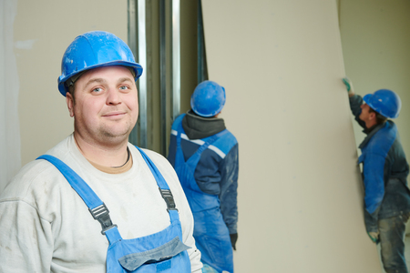 gypsum: Portrait of builder in front of gypsum plasterboard installation during indoor walling by workers Stock Photo