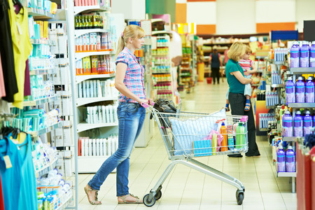 household goods: Shopping woman with cart in supermarket store buying household goods Stock Photo