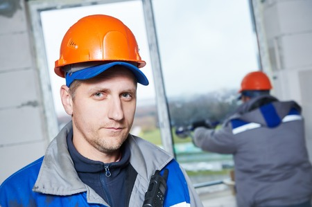 many windows: Portrait of male industrial builder worker at window installation in building construction site