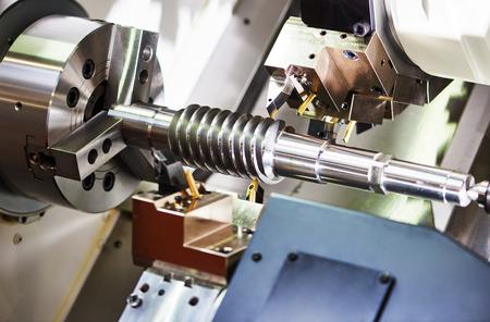 metaalverwerkende industrie. snijgereedschap verwerking van staal metalen spiraal rondsel of worm schroefas op draaibank machine in de werkplaats. Focus op tool.