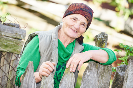 rural community: Portrait of Georgian happy senior countrywoman outdoors wearing woolen headscarf Stock Photo