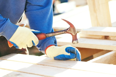 nailing: Joinery and carpentry. A closeup of male carpenter worker hands hammering nail into board outdoors