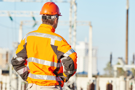 high visibility: Engineering supervision. Male service engineer in high visibility reflecting clothing and hard hat standing outdoors in front of heat electropower station