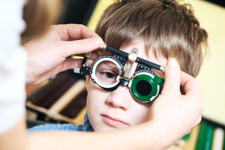 specs: Optometry concept. Young boy with phoropter during sight testing or eye examinations in ophthalmological clinic Stock Photo