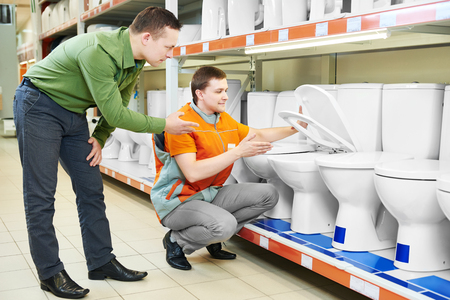 salesperson: Shopping. Hardware store salesperson assistant helping young man choosing toilet bowl