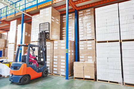 rack arrangement: warehousing. Forklift driver stacking pallets with package boxes by stacker loader Stock Photo
