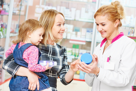 pharmacy store: pharmacist chemist woman demonstrating vitamin to child girl with mother in pharmacy drugstore. family health Stock Photo