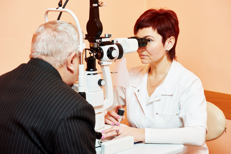 doctor of optometry: Optometry concept. female optometrist optician doctor examines eyesight of female patient in eye ophthalmological clinic Stock Photo