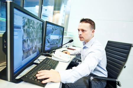 Oficer straży bezpieczeństwa obserwując monitorowania systemu bezpieczeństwa nadzoru wideo Zdjęcie Seryjne