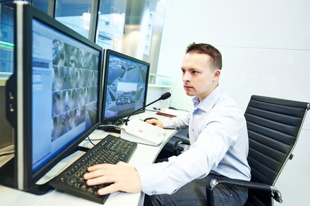 thief: security guard officer watching video monitoring surveillance security system Stock Photo