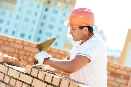 Bauarbeiter. mason Maurer Installation aus rotem Backstein mit Kelle Spachtel im Freien