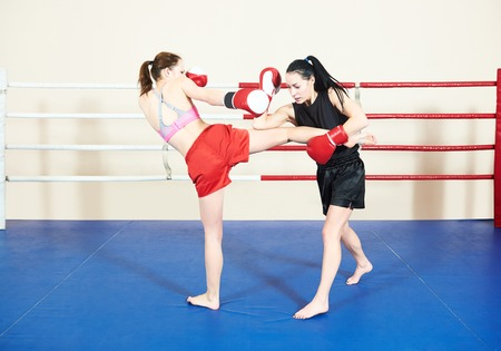 phisical: Thai kickboxing match. Muay thai female boxers fighting at training boxing ring