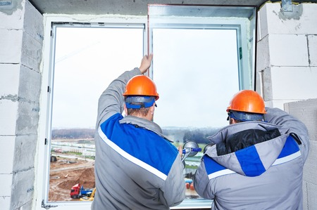 installation: male industrial builders worker at window installation in building construction site Stock Photo