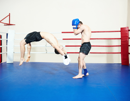 phisical: Thai kickboxing. Muay thai fighters at training boxing ring