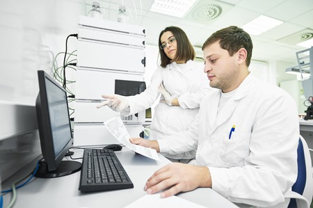 operative system: Pharmaceutical scientific researchers analyzing liquid chromatography data at pharmacy industry manufacture factory laboratory