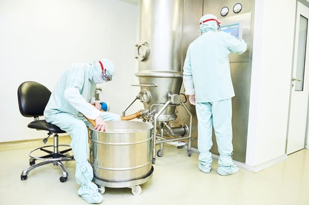 Pharmaceutical industry. Pharmaceutical factory workers operating pharma granulator dryer and fluid bed system at pharmaceutical factory