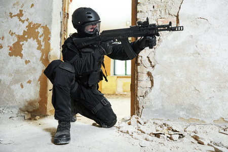 antiterrorist: Military industry. Special forces or anti-terrorist police soldier,  private military contractor armed with assault rifle ready to attack during clean-up operation, mission
