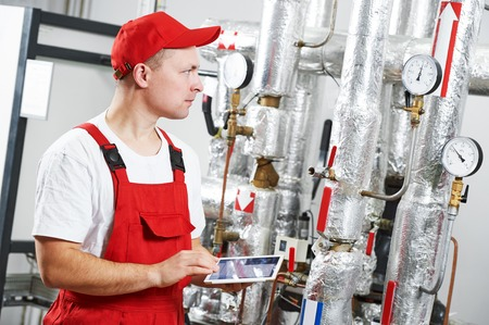 Technician maintenance repairman engineer inspecting heating system in boiler room Stock Photo