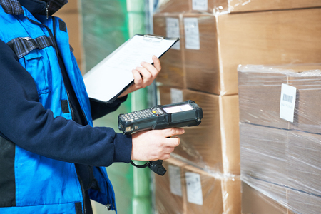 warehouse equipment: Male worker scanning package with barcode scanner in modern warehouse