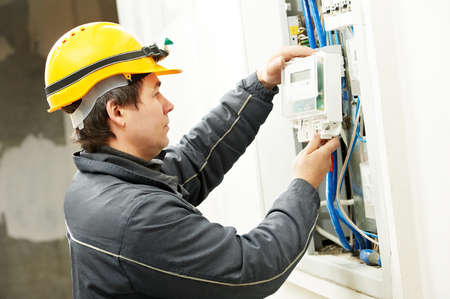 electric line: electrician builder at work installing energy saving meter into electric line distribution fuseboard
