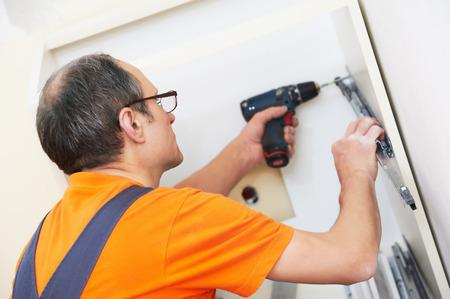 kitchen furniture: Craftsman carpenter worker at kitchen furniture set installation service work Stock Photo