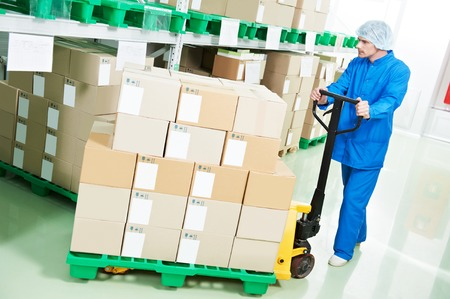 medical warehouse worker man loading boxes with medcine drugs by hand forklift at pharmacy factory