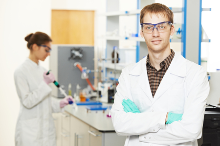 lb: Pharmacy and chemistry theme. Portrait of male scientific researcher in front of female lb worker making medicine experiment at pharmacy microbiology laboratory Stock Photo