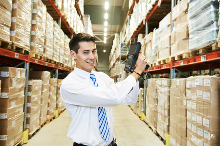 Male manager worker with barcode scanner in modern warehouse