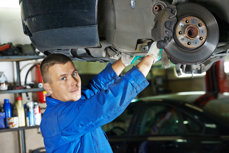 disassembly: portrait of car mechanic worker inspecting and repairing suspension of lifted automobile at auto repair garage shop station