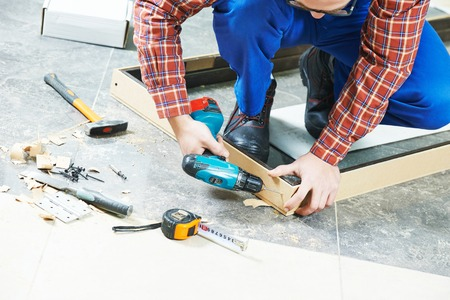 joiner: Carpenter joiner worker preparing door frame for indoor installation