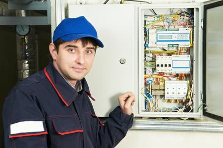 Jonge volwassen elektricien bouwer ingenieur in de buurt van de distributie switch-apparatuur in zekeringenkast