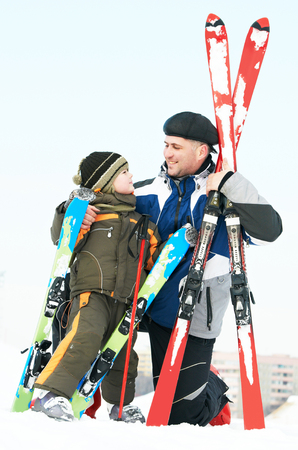 children sport: Happy family, smiling little boy and father, in warm winter clothing with skis outdoors. Ready to ski.