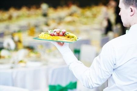 Servicio de catering. Camarero mano del hombre con la fruta en el restaurante