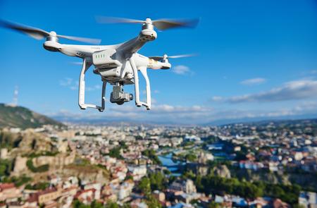 Drone quadcopter s vysokým rozlišením digitální fotoaparát létání nebo vznášející se v modré obloze nad městem