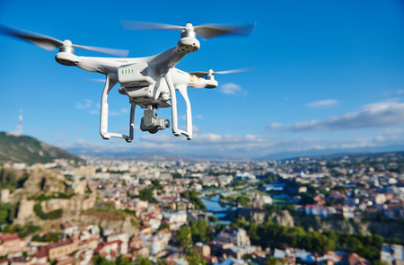 drone quadcopter with high resolution digital camera flying or hovering in blue sky over the city