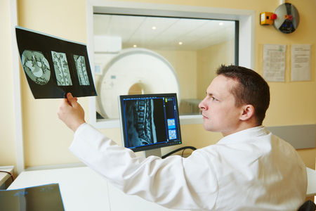 medics: Computed tomography or MRI scanner test. male radiologist doctor man examining x-ray image on digital display. Toned