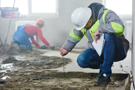 capataz constructor medida ingeniero inspector de piso que cubre al sitio de construcción en interiores en el nuevo edificio de apartamentos cubierta plana Foto de archivo