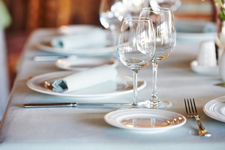 wine glasses: catering services. glasses for wine and dishes plates with cutlery in restaurant before event