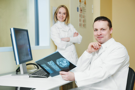 computed: Computed tomography or MRI scanner test. Team of radiologist woman and man with x-ray image on digital display Stock Photo