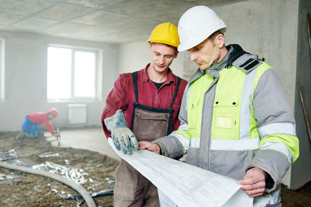 rennovation: foreman builder and construction worker with blueprint discussing floor covering in new building or repairing indoor flat apartment Stock Photo