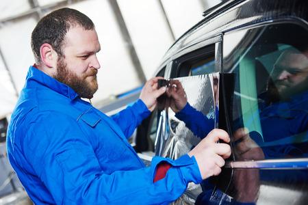 tinting: car tinting. Automobile mechanic technician applying foil on  window in repair garage workshop Stock Photo