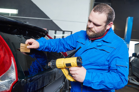 protective: car tinting. Automobile mechanic technician applying foil on  window in repair garage workshop Stock Photo
