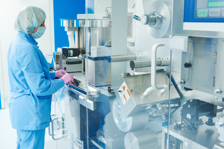 Pharmaceutics. Pharmaceutical industry worker operates blister and cartoning packaging machine at factory Stock Photo