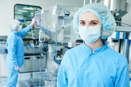 Pharmaceutics. Pharmaceutical industry female worker portrait in front of blister and cartoning packaging machine at factory