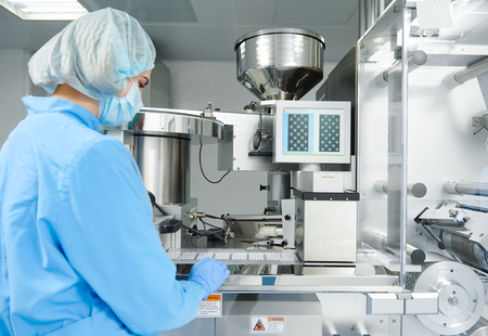 drug: Pharmaceutics. Pharmaceutical industry worker operates blister and cartoning packaging machine at factory Stock Photo