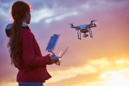 drone quadcopter volando o flotando por debajo de operación de control remoto en la puesta del sol. campo muy baja de la visión
