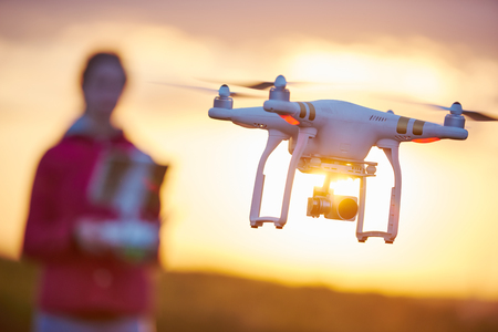 drone quadcopter flying or hovering by under remote control operation in sunset. Very shallow field of view Reklamní fotografie