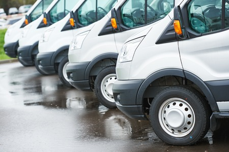 transporting: freight services. commercial delivery vans in row at transporting carrier shipping service company parking
